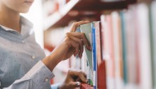Woman at the library, she is searching books on the bookshelf and taking a textbook on the shelf, hand close up