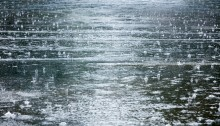flooded road during heavy rain. raindrops splashes background.