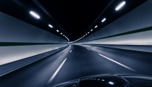 Empty freeway headed into a lighted tunnel
